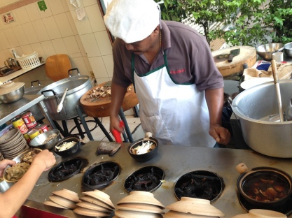 Chef preparing each clay pot to specialized orders of meat and vegetable