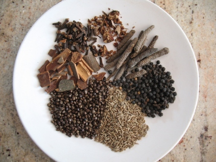 "spices for mekelesha clockwise from bottom: cumin seed, korerima ""false cardamom"", cassia bark, cloves, nutmeg, long pepper, black peppercorn"
